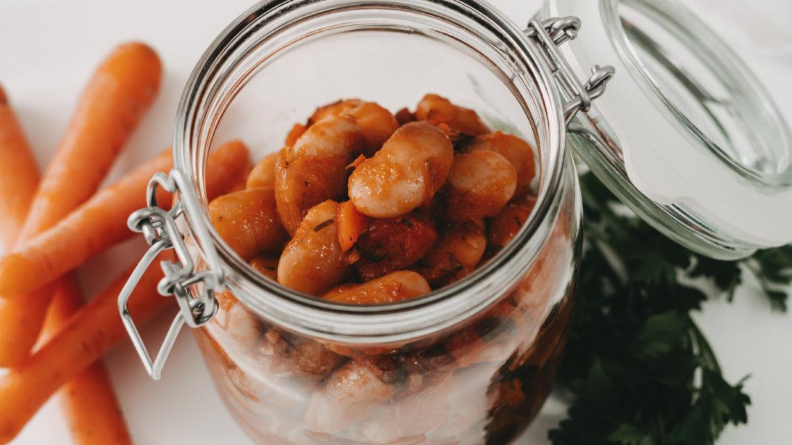 griechische Riesenbohnen im Glas, Karotten im Hintergrund