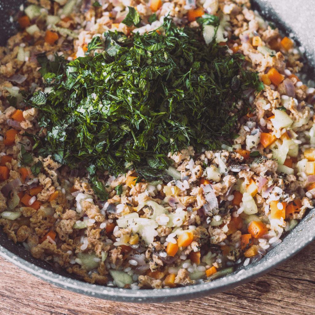 Reis-Veggi-Hackfüllung mit frischen Kräutern in einer Bratpfanne