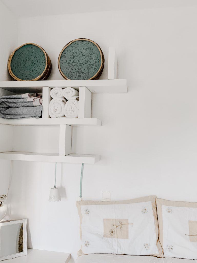 Weiße Regal an einer Wand, helle Kissen auf einem Bett