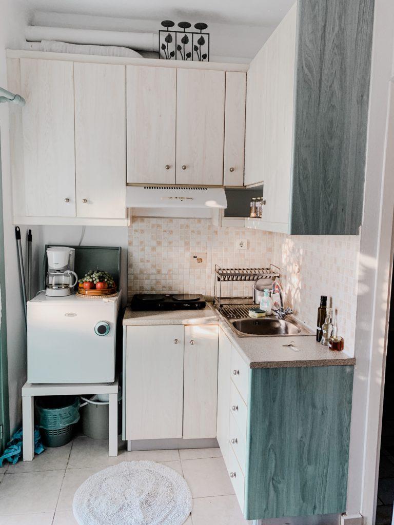 eine kleine Küche mit Kühlschrank und Spülbecken