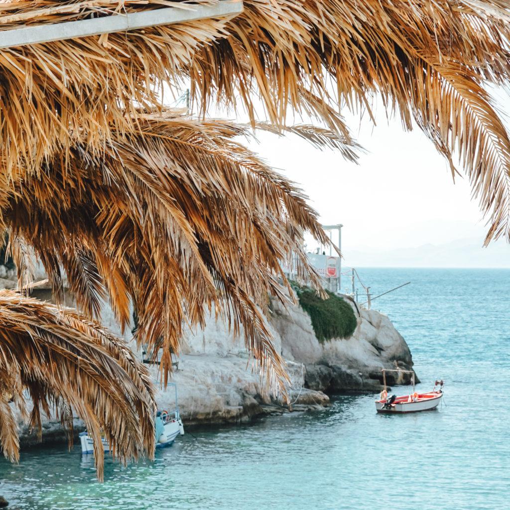 Palmenwedel vor blauem Wasser und kleinem Boot in Matala