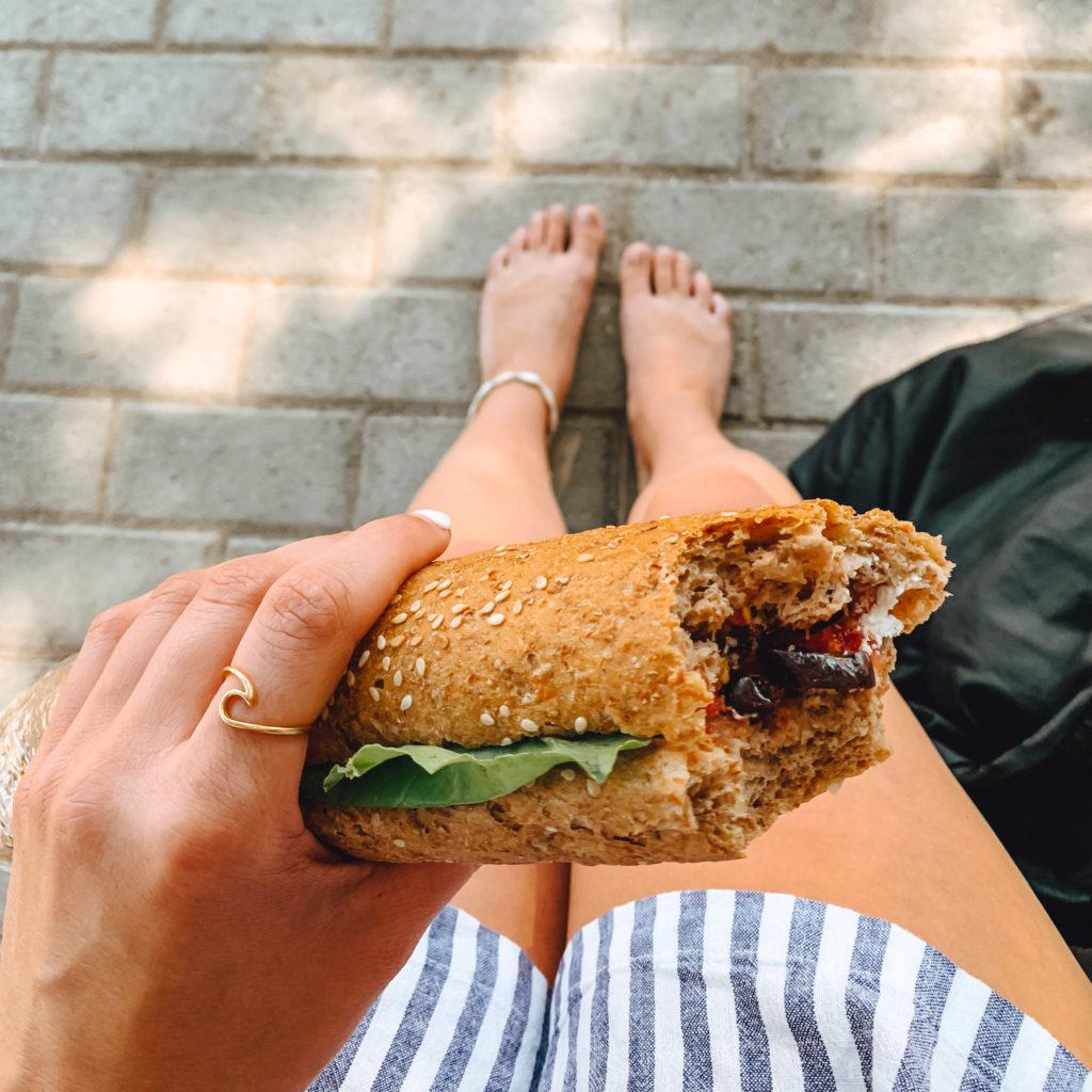 Ein angebissenes Sandwich in der Hand eines Mädchens