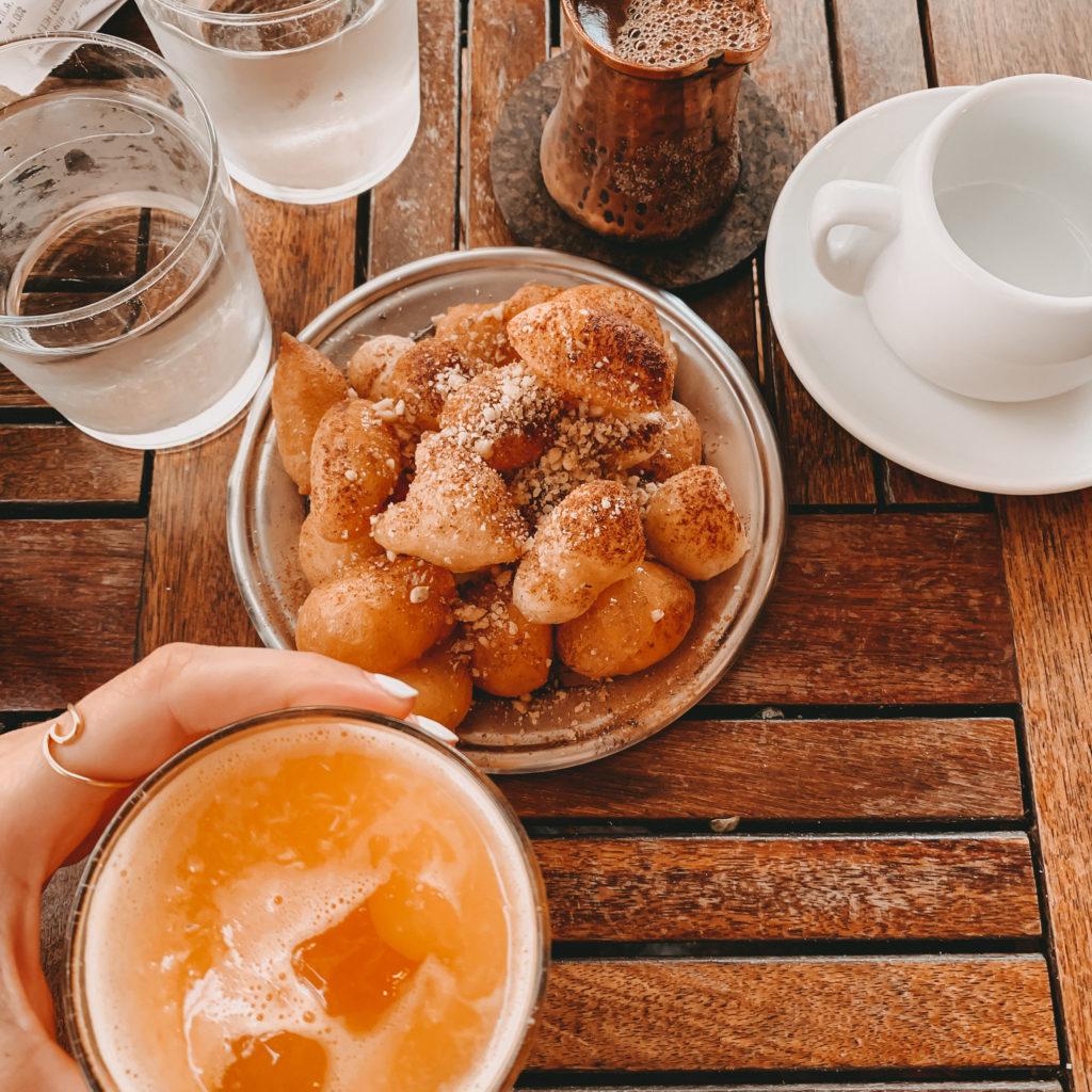 Loukoumades, frisch gepresster Orangensaft, Wassergläser und ein griechischer Macke im Kännchen