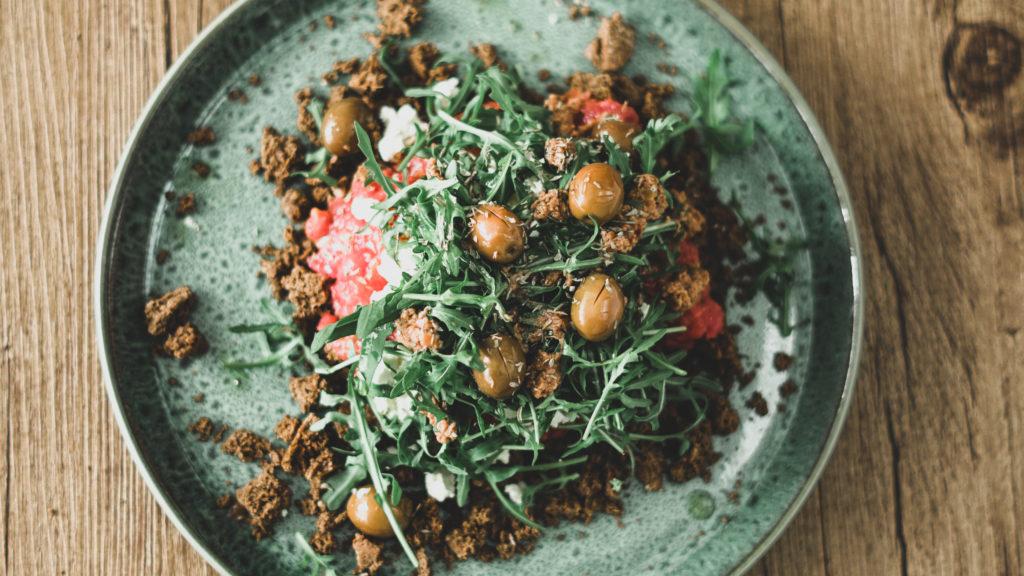 Dakos Salat mit Rucola und Oliven auf einem türkisen Teller