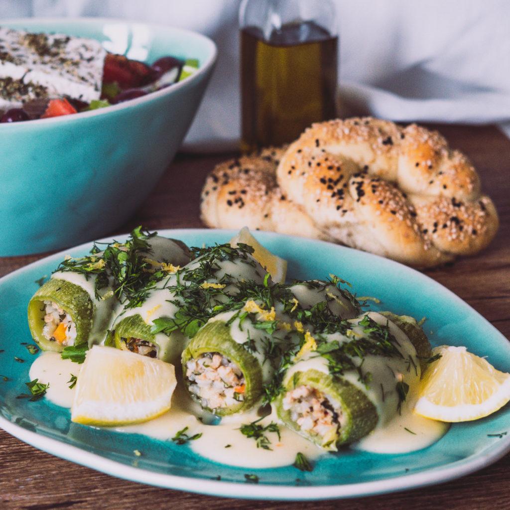 Gefüllte Zucchini mit Zitrone auf einem türkisen Teller, Sesamringe und Salat im Hintergrund