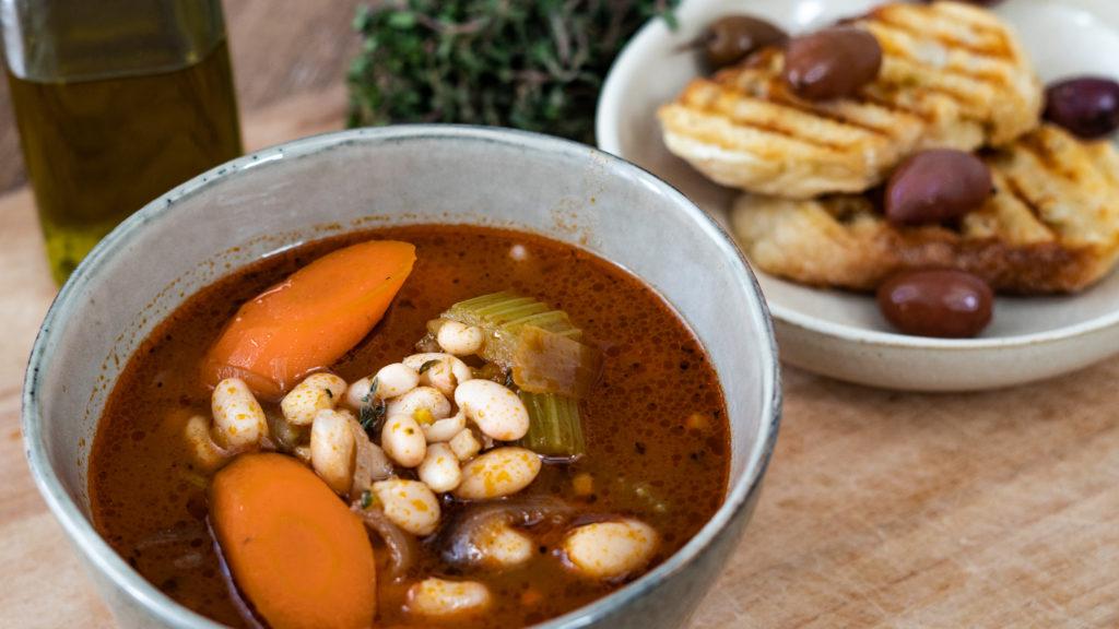 eine Schale mit griechischer Bohnensuppe, Brot und Oliven im Hintergrund