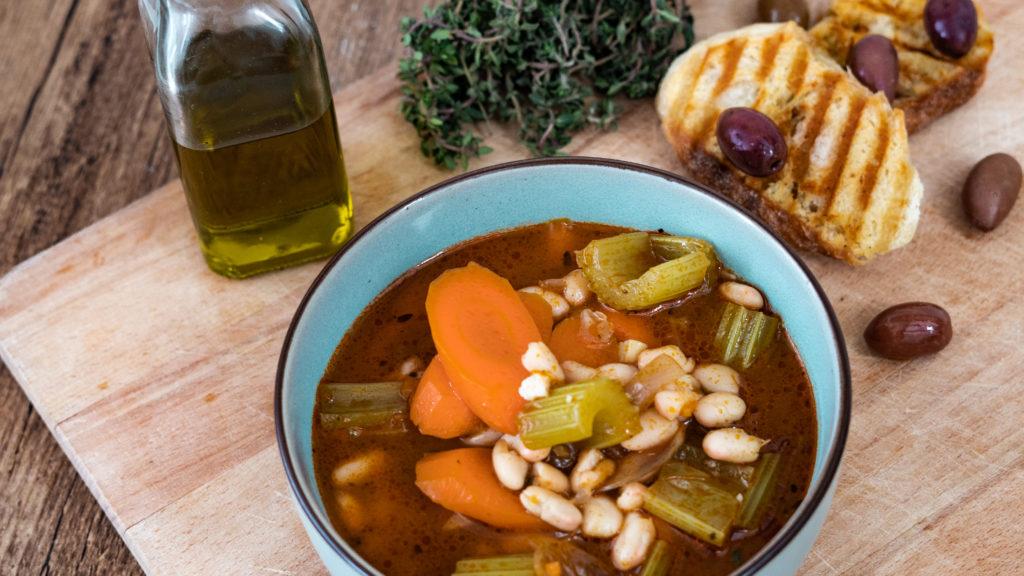 Buntes Gemüse in einer roten Bohnensuppe auf einem Holzbrett. Brot, Oliven, Thymian und Olivenöl im Hintergrund.