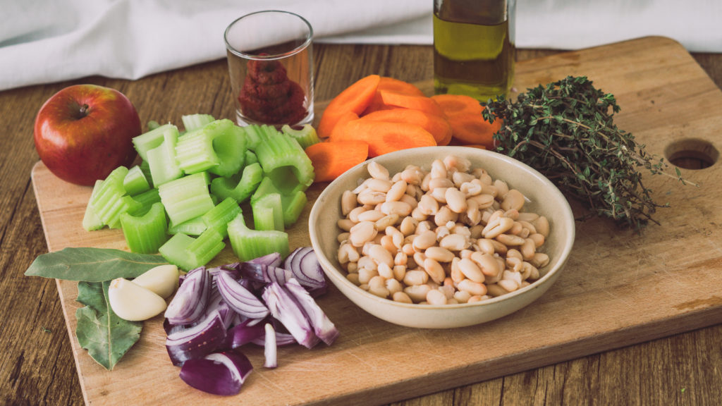 Gehacktes Gemüse für eine griechische Bohnensuppe auf einem großen Holzbrett