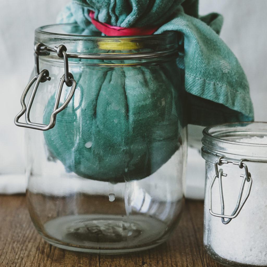 Ein Tuch voller Joghurt in einem Einmachglas,  grobes Salz daneben