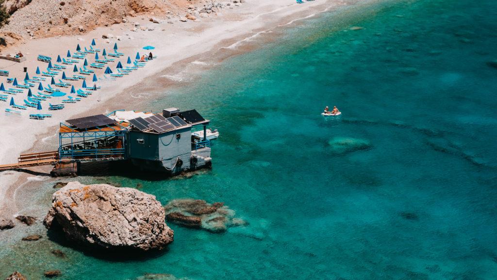 Ein Bild vom Strand von Glyka Nera mit einer Taverne, die auf dem Wasser schwimmt.