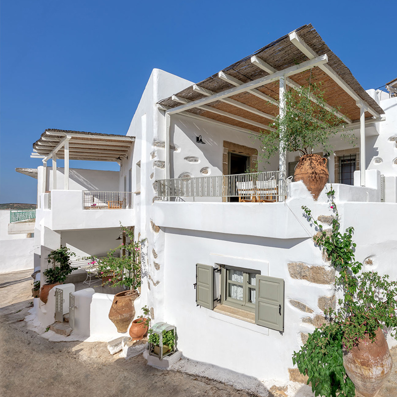 Weisses griechisches Steinhaus mit Boho Terrassen